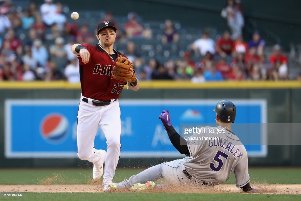 Infeilder Brandon Drury #27 of the Arizona Diamondbacks throws over the sliding Carlos Gonzalez #5 of the Colorado Rockies to complete a double play during the 11th inning of the MLB game at Chase Field on April 30, 2017 in Phoenix, Arizona.