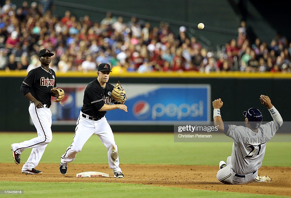 Infielder <a gi-track='captionPersonalityLinkClicked' href=/galleries/search?phrase=Aaron+Hill+-+Baseball+Player&family=editorial&specificpeople=239242 ng-click='$event.stopPropagation()'>Aaron Hill</a> #2 of the Arizona Diamondbacks throws over the sliding Juan Francisco #21 of the Milwaukee Brewers to complete a double play during the sixth inning of the MLB game at Chase Field on July 13, 2013 in Phoenix, Arizona.