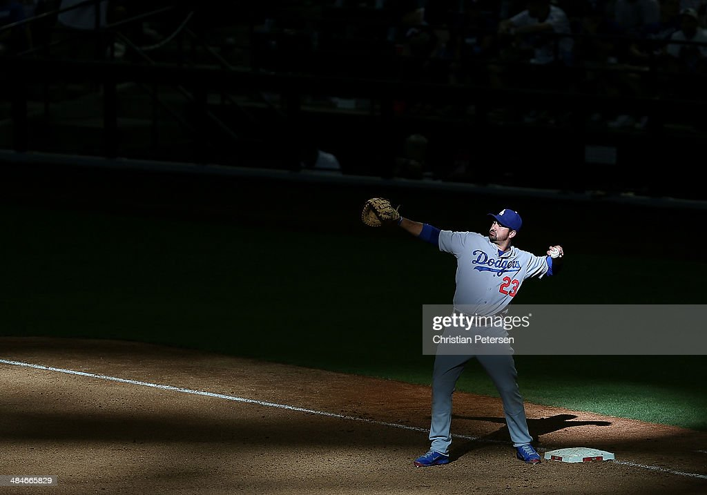 Infielder Adrian Gonzalez #23 of the Los Angeles Dodgers warms up at first base during the ninth inning of the MLB game against the Arizona Diamondbacks at Chase Field on April 13, 2014 in Phoenix, Arizona. The Dodgers defeated the Diamondbacks 8-6.