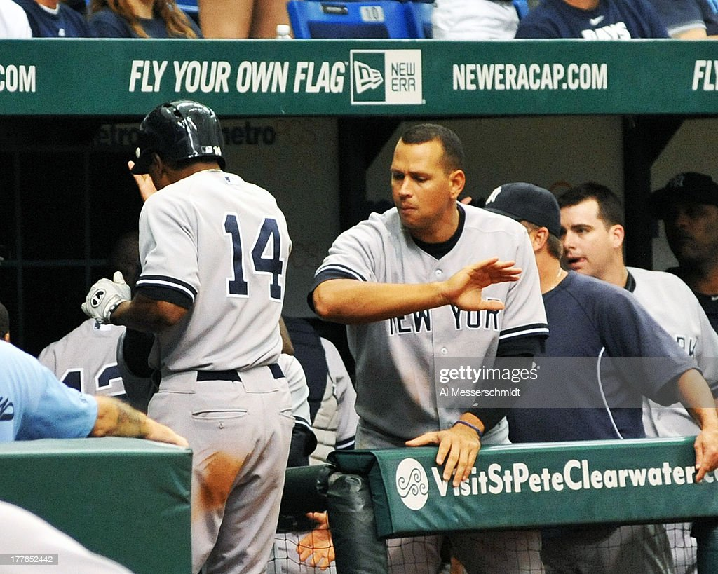 Infielder Alex Rodriguez of the New York Yankees celebrates after outfielder Curtis Granderson #14 drives in the winning run in the 11th inning against the Tampa Bay Rays August 25, 2013 at Tropicana Field in St. Petersburg, Florida. The Yankees won 3 - 2.
