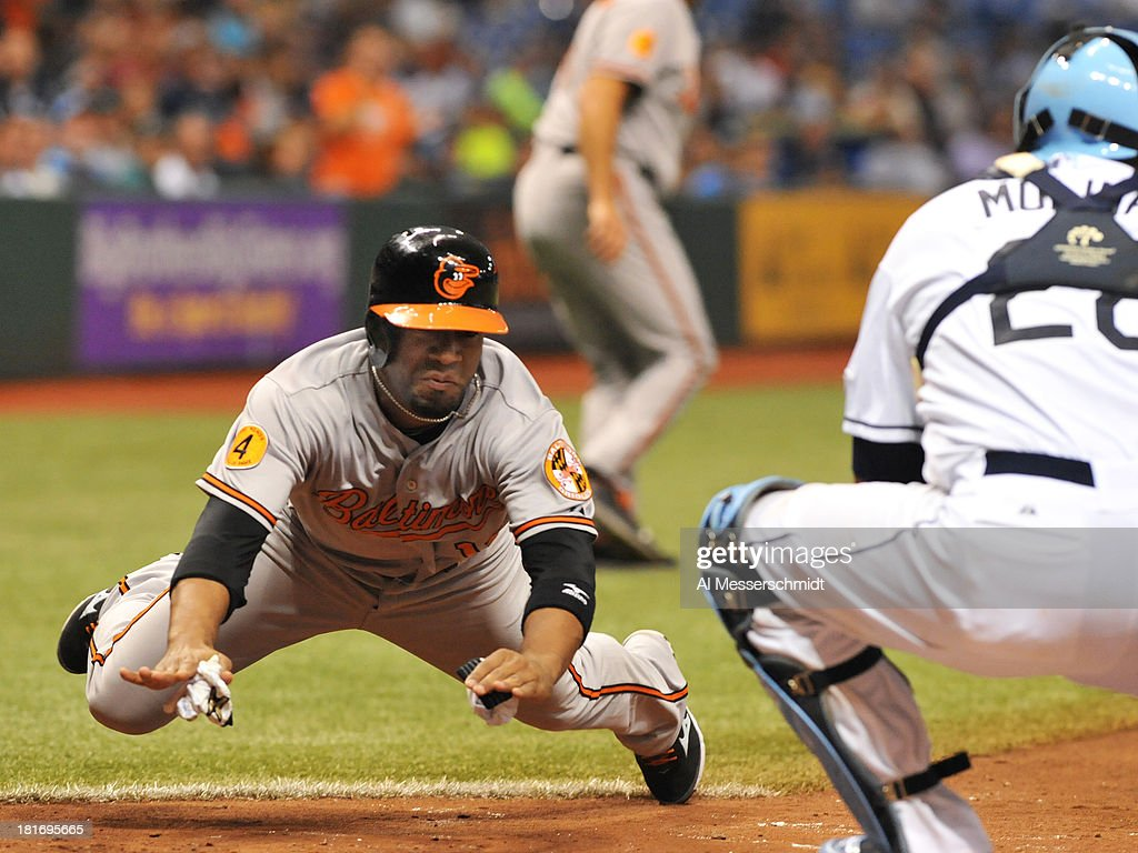 Infielder Alexi Casilla of the Baltimore Orioles slides into home plate in the 7th inning against the Tampa Bay Rays September 23 2013 at Tropicana...