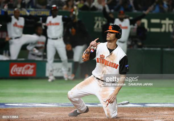 Infielder Andrelton Simmons of the Netherlands slides to the home plate to score a run by a sacrifice fly of Infielder Xander Bogaerts to make it 53...