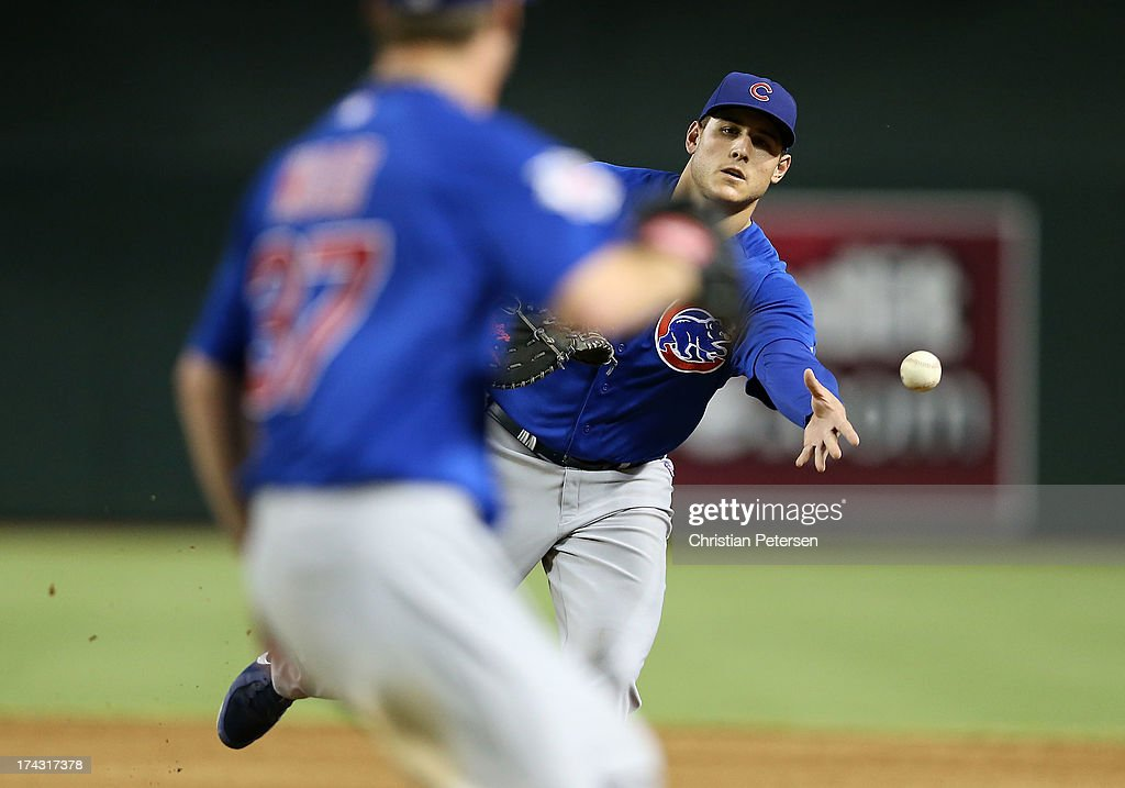 Infielder <a gi-track='captionPersonalityLinkClicked' href=/galleries/search?phrase=Anthony+Rizzo&family=editorial&specificpeople=7551494 ng-click='$event.stopPropagation()'>Anthony Rizzo</a> #44 of the Chicago Cubs flips the ball to pitcher Travis Wood #37 for an out against the Arizona Diamondbacks during the MLB game at Chase Field on July 23, 2013 in Phoenix, Arizona.
