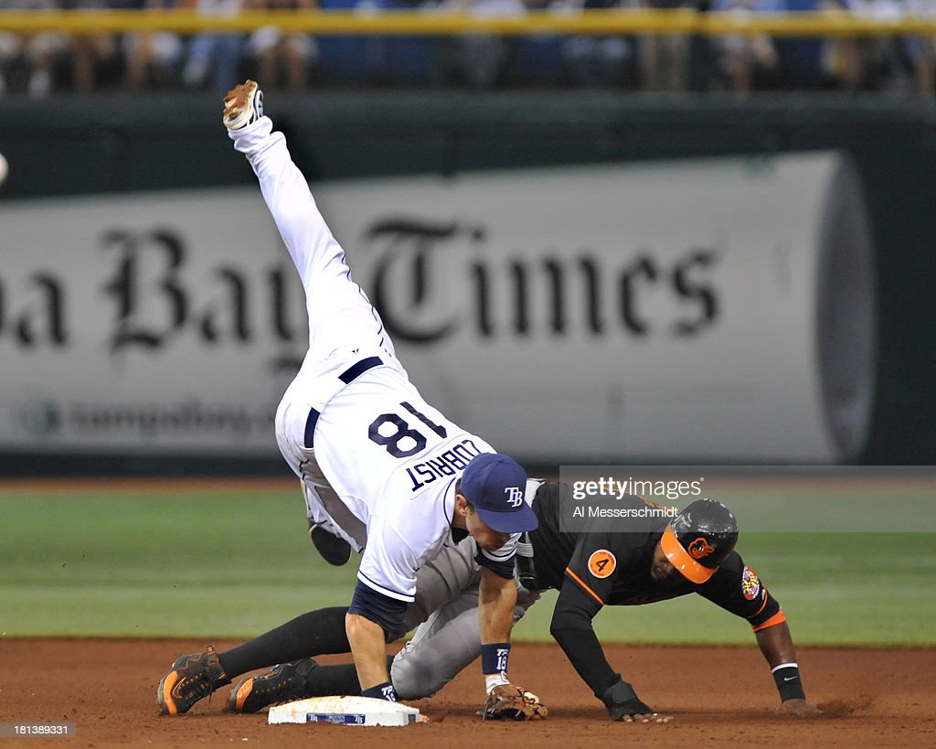 Infielder Ben Zobrist #18 of the Tampa Bay Rays tumbles over outfielder Adam Jones #10 of the Baltimore Orioles after throwing to 1st base for a double play September 20, 2013 at Tropicana Field in St. Petersburg, Florida.