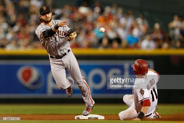 Infielder Brandon Crawford of the San Francisco Giants throws over the sliding AJ Pollock of the Arizona Diamondbacks to complete a double play...