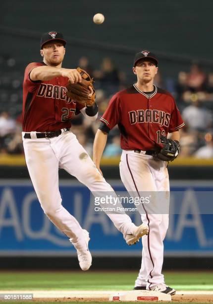 Infielder Brandon Drury of the Arizona Diamondbacks fields a ground ball out alongside Nick Ahmed during the MLB game against the Philadelphia...