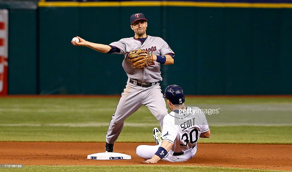 Infielder Brian Dozier of the Minnesota Twins attempts to turn a double play as Luke Scott of the Tampa Bay Rays breaks it up during the game at...