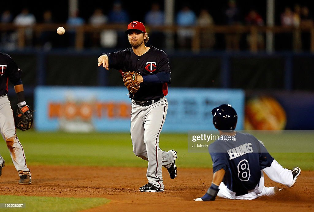 Infielder <a gi-track='captionPersonalityLinkClicked' href=/galleries/search?phrase=Brian+Dozier&family=editorial&specificpeople=7553002 ng-click='$event.stopPropagation()'>Brian Dozier</a> #2 of the Minnesota Twins turns the double play as outfielder <a gi-track='captionPersonalityLinkClicked' href=/galleries/search?phrase=Desmond+Jennings&family=editorial&specificpeople=5974085 ng-click='$event.stopPropagation()'>Desmond Jennings</a> #8 of the Tampa Bay Rays is out at second base during a Grapefruit League spring training game at the Charlotte Sports Complex on March 11, 2013 in Port Charlotte, Florida.