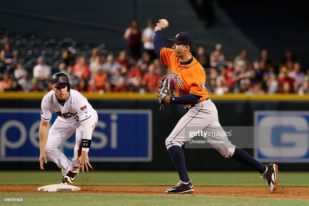 Infielder <a gi-track='captionPersonalityLinkClicked' href=/galleries/search?phrase=Carlos+Correa+-+Baseball+Player&family=editorial&specificpeople=11452157 ng-click='$event.stopPropagation()'>Carlos Correa</a> #1 of the Houston Astros throws to first base after getting a force out at second base on the sliding Brandon Drury #27 of the Arizona Diamondbacks during the first inning of the MLB game at Chase Field on May 31, 2016 in Phoenix, Arizona.