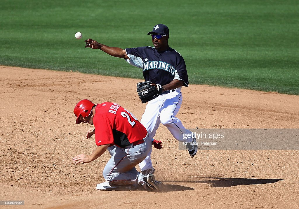 Infielder Chone Figgins #9 of the Seattle Mariners throws over the sliding Chris Heisey #28 of the Cincinnati Reds for a force out during the fourth inning of the spring training game at Peoria Stadium on March 6, 2012 in Peoria, Arizona.
