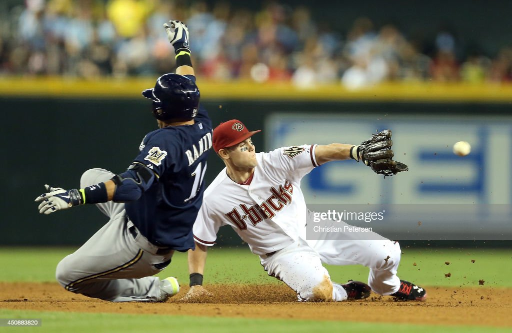 Infielder Chris Owings of the Arizona Diamondbacks catches the ball late as Aramis Ramirez of the Milwaukee Brewers slides into second base after...