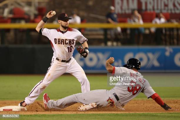 Infielder Chris Owings of the Arizona Diamondbacks throws over the sliding Jose Martinez of the St Louis Cardinals to compete a double play during...
