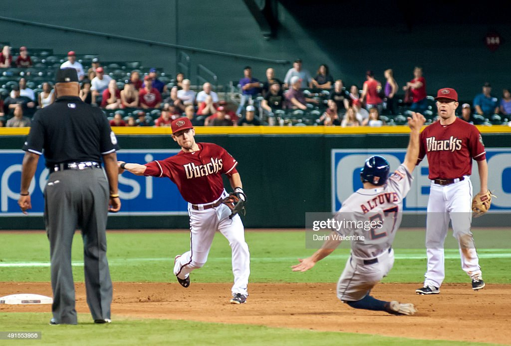 Infielder Chris Owings of the Arizona Diamondbacks turns a ninth inning double play as Jose Altuve of the Houston Astros slides into second base with...