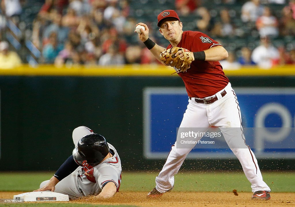 Infielder Cliff Pennington of the Arizona Diamondbacks gets a force out at second base on Chris Johnson of the Atlanta Braves during the seventh...