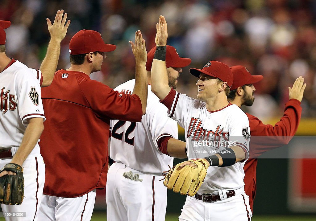 Infielder Cliff Pennington of the Arizona Diamondbacks highfives teammates after defeating the Los Angeles Dodgers in the MLB game at Chase Field on...