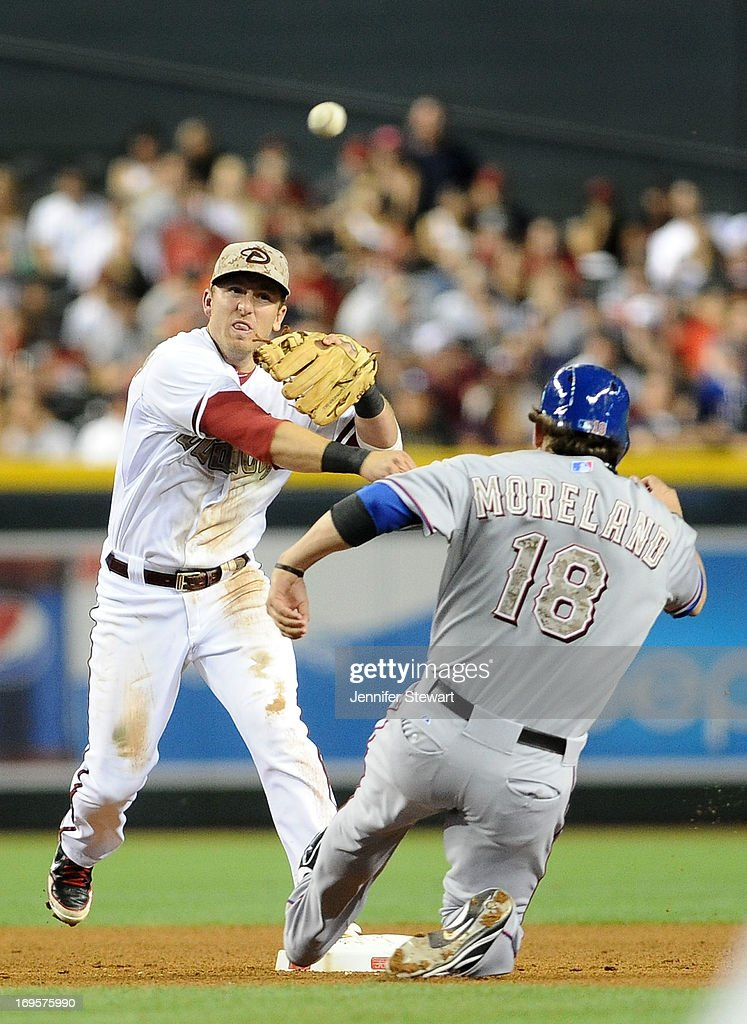 Infielder Cliff Pennington of the Arizona Diamondbacks turns a double play as Mitch Moreland of the Texas Rangers slides into second base in the...