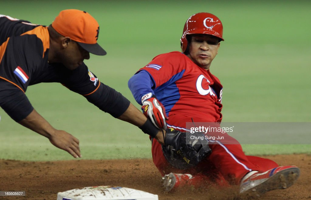 Infielder Curt Smith # 18 of Netherlands tags out Frederich Cepeda # 24 of Cuba as he slides into first base during the World Baseball Classic Second Round Pool 1 game between Cuba and the Netherlands at Tokyo Dome on March 11, 2013 in Tokyo, Japan.