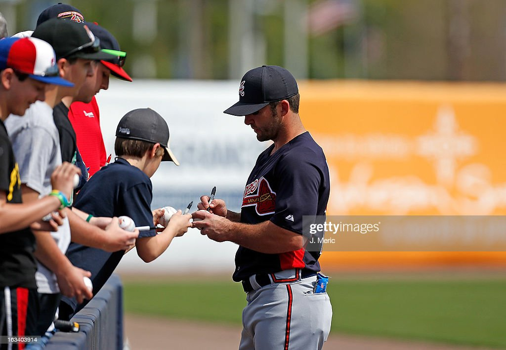 Infielder Dan Uggla #26 of the Atlanta Braves signs an autograph just before the start of the Grapefruit League Spring Training Game against the New York Yankees at George M. Steinbrenner Field on March 9, 2013 in Tampa, Florida.