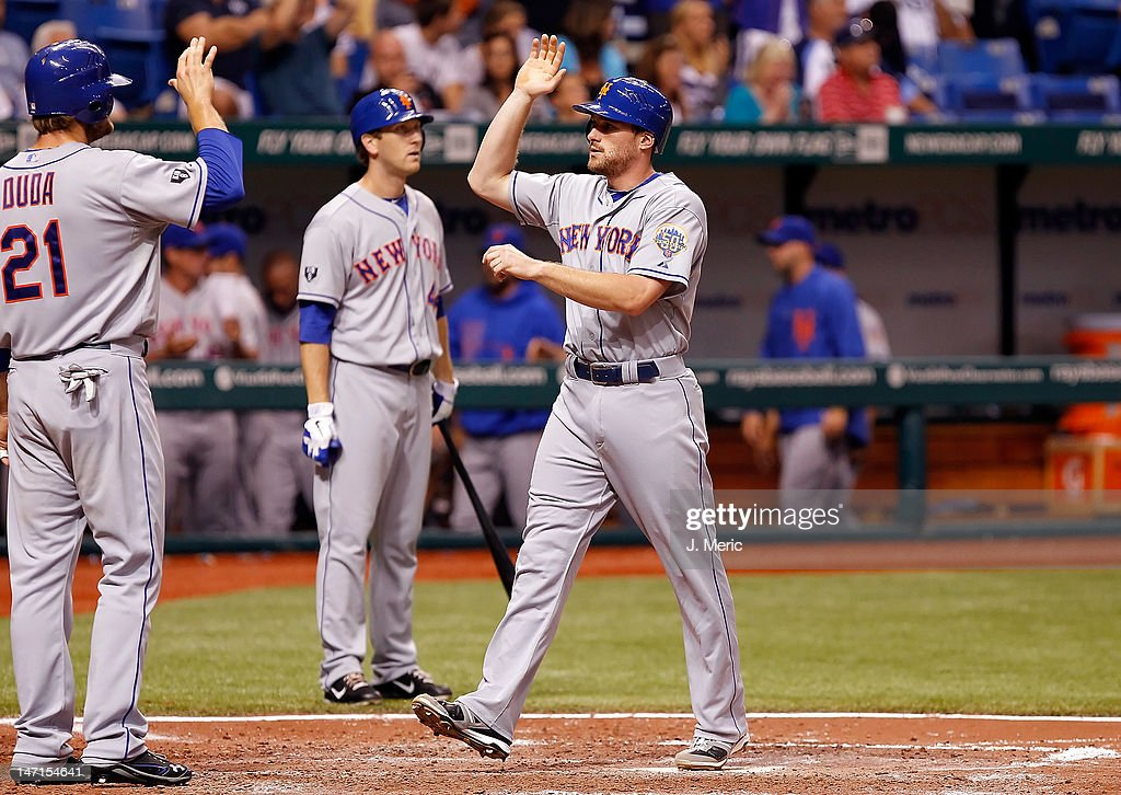 Infielder Daniel Murphy #28 of the New York Mets is congratulated after scoring against the Tampa Bay Rays during the game at Tropicana Field on June 12, 2012 in St. Petersburg, Florida.