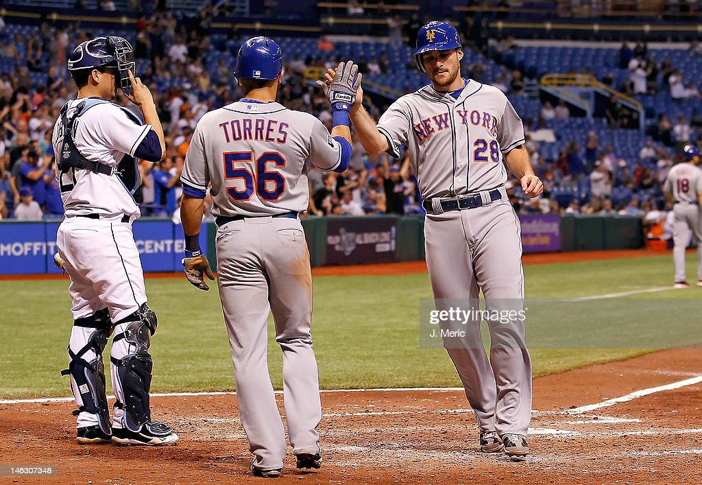 Infielder Daniel Murphy #28 of the New York Mets is congratulated by teammate <a gi-track='captionPersonalityLinkClicked' href=/galleries/search?phrase=Andres+Torres&family=editorial&specificpeople=835839 ng-click='$event.stopPropagation()'>Andres Torres</a> #56 after scoring against the Tampa Bay Rays during the game at Tropicana Field on June 13, 2012 in St. Petersburg, Florida.