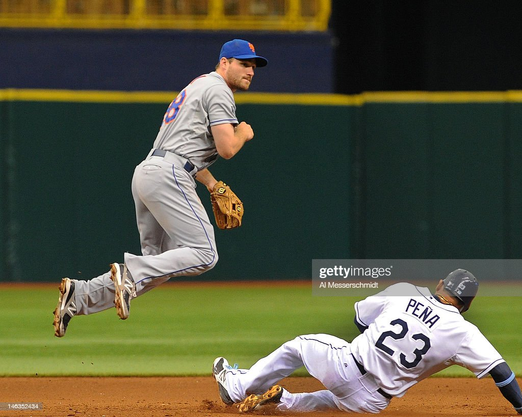 Infielder Daniel Murpy #28 of the New York Mets completes a double-play throw over sliding infielder Carlos Pena #23 of the Tampa Bay Rays June 14, 2012 at Tropicana Field in St. Petersburg, Florida. The Mets won 9 - 6.