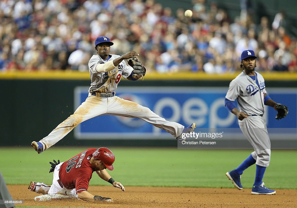 Infielder Dee Gordon #9 of the Los Angeles Dodgers makes a leaping throw over the sliding Chris Owings #16 of the Arizona Diamondbacks to complete a double play during the fourth inning of the MLB game at Chase Field on April 13, 2014 in Phoenix, Arizona.