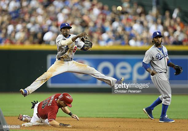 Infielder Dee Gordon of the Los Angeles Dodgers makes a leaping throw over the sliding Chris Owings of the Arizona Diamondbacks to complete a double...