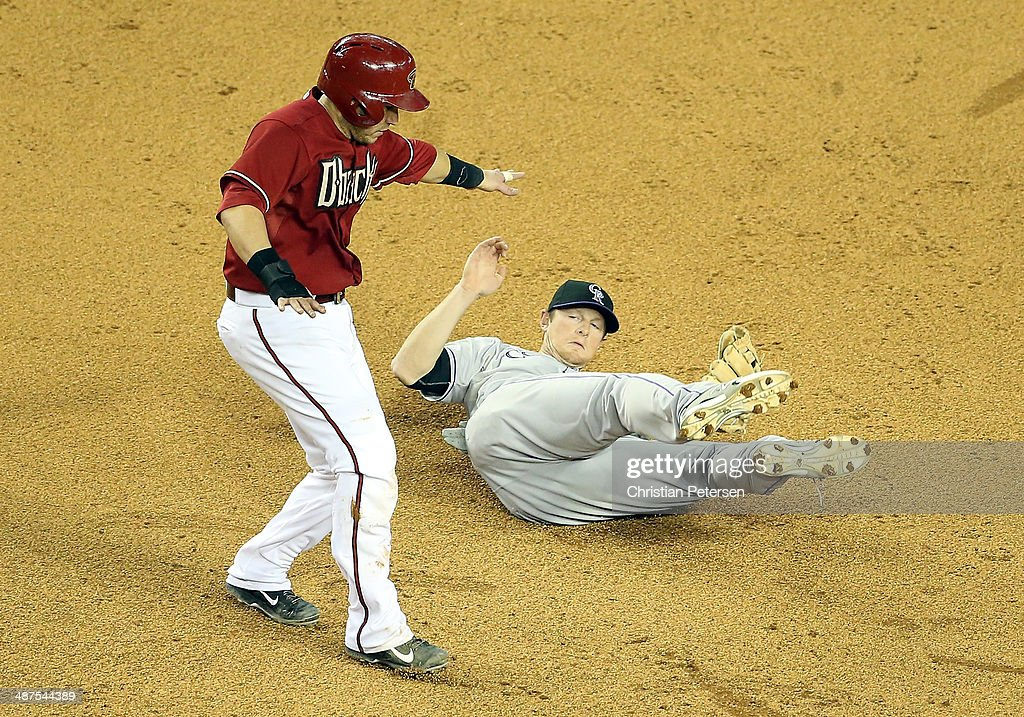 Infielder DJ LeMahieu #9 of the Colorado Rockies falls to the ground after a collision with Miguel Montero #26 of the Arizona Diamondbacks as he broke up a double play during the sixth inning of the MLB game at Chase Field on April 30, 2014 in Phoenix, Arizona.