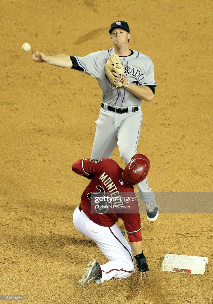 Infielder DJ LeMahieu #9 of the Colorado Rockies throws over the sliding Miguel Montero #26 of the Arizona Diamondbacks as he attempts to complete an unsuccessful double play during the sixth inning of the MLB game at Chase Field on April 30, 2014 in Phoenix, Arizona.