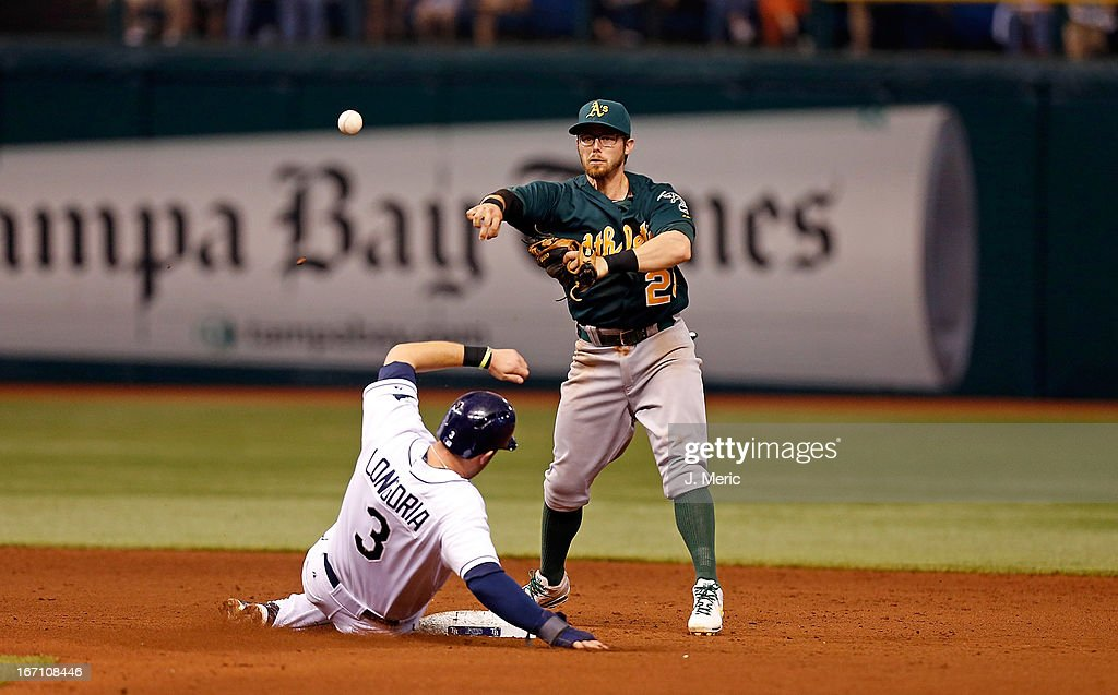 Infielder <a gi-track='captionPersonalityLinkClicked' href=/galleries/search?phrase=Eric+Sogard&family=editorial&specificpeople=6796459 ng-click='$event.stopPropagation()'>Eric Sogard</a> #28 of the Oakland Athletics turns a double play as <a gi-track='captionPersonalityLinkClicked' href=/galleries/search?phrase=Evan+Longoria&family=editorial&specificpeople=2349329 ng-click='$event.stopPropagation()'>Evan Longoria</a> #3 of the Tampa Bay Rays tries to break it up during the game at Tropicana Field on April 20, 2013 in St. Petersburg, Florida.