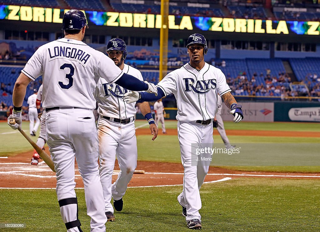 Infielder <a gi-track='captionPersonalityLinkClicked' href=/galleries/search?phrase=Evan+Longoria&family=editorial&specificpeople=2349329 ng-click='$event.stopPropagation()'>Evan Longoria</a> #3 of the Tampa Bay Rays congratulates <a gi-track='captionPersonalityLinkClicked' href=/galleries/search?phrase=Sean+Rodriguez&family=editorial&specificpeople=4171805 ng-click='$event.stopPropagation()'>Sean Rodriguez</a> #1 and <a gi-track='captionPersonalityLinkClicked' href=/galleries/search?phrase=Desmond+Jennings&family=editorial&specificpeople=5974085 ng-click='$event.stopPropagation()'>Desmond Jennings</a> #8 after they scored against the Boston Red Sox during the game at Tropicana Field on September 18, 2012 in St. Petersburg, Florida.