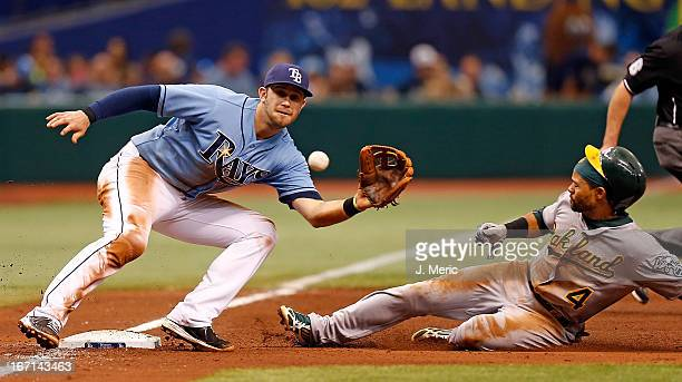 Infielder Evan Longoria of the Tampa Bay Rays takes the throw at third as designated hitter Coco Crisp of the Oakland Athletics steals third during...