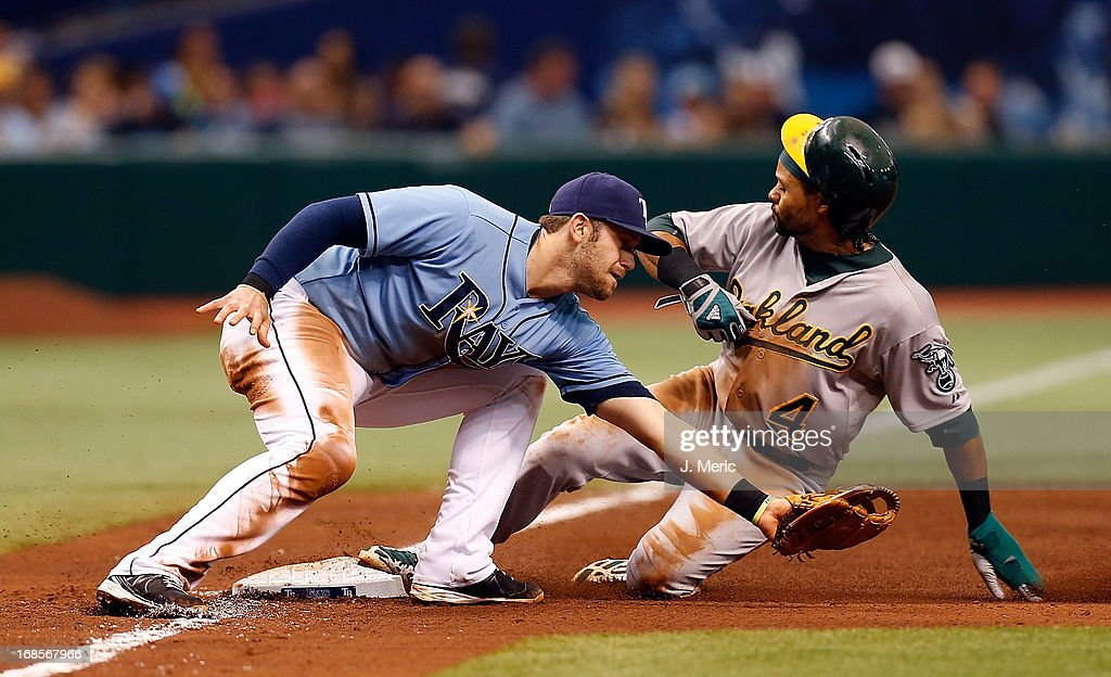 Infielder <a gi-track='captionPersonalityLinkClicked' href=/galleries/search?phrase=Evan+Longoria&family=editorial&specificpeople=2349329 ng-click='$event.stopPropagation()'>Evan Longoria</a> #3 of the Tampa Bay Rays takes the throw at third as designated hitter <a gi-track='captionPersonalityLinkClicked' href=/galleries/search?phrase=Coco+Crisp&family=editorial&specificpeople=206376 ng-click='$event.stopPropagation()'>Coco Crisp</a> #4 of the Oakland Athletics steals third during the game at Tropicana Field on April 21, 2013 in St. Petersburg, Florida.