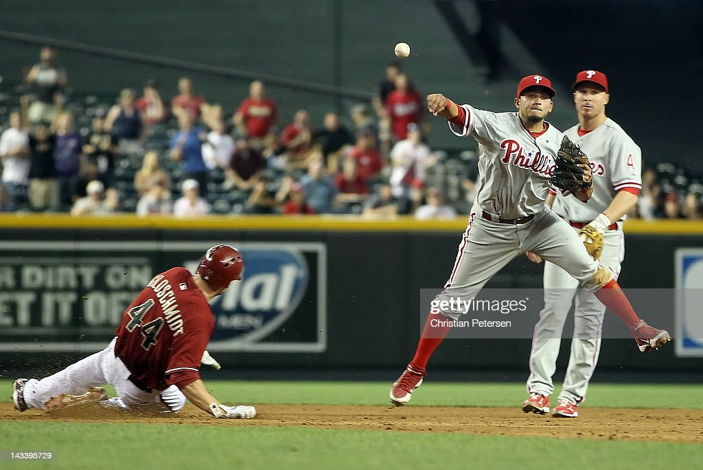 Infielder Freddy Galvis of the Philadelphia Phillies throws over the sliding Paul Goldschmidt of the Arizona Diamondbacks to complete a double play...