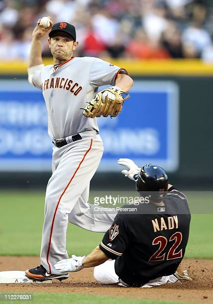 Infielder Freddy Sanchez of the San Francisco Giants throws over the sliding Xavier Nady of the Arizona Diamondbacks attempting a double play during...