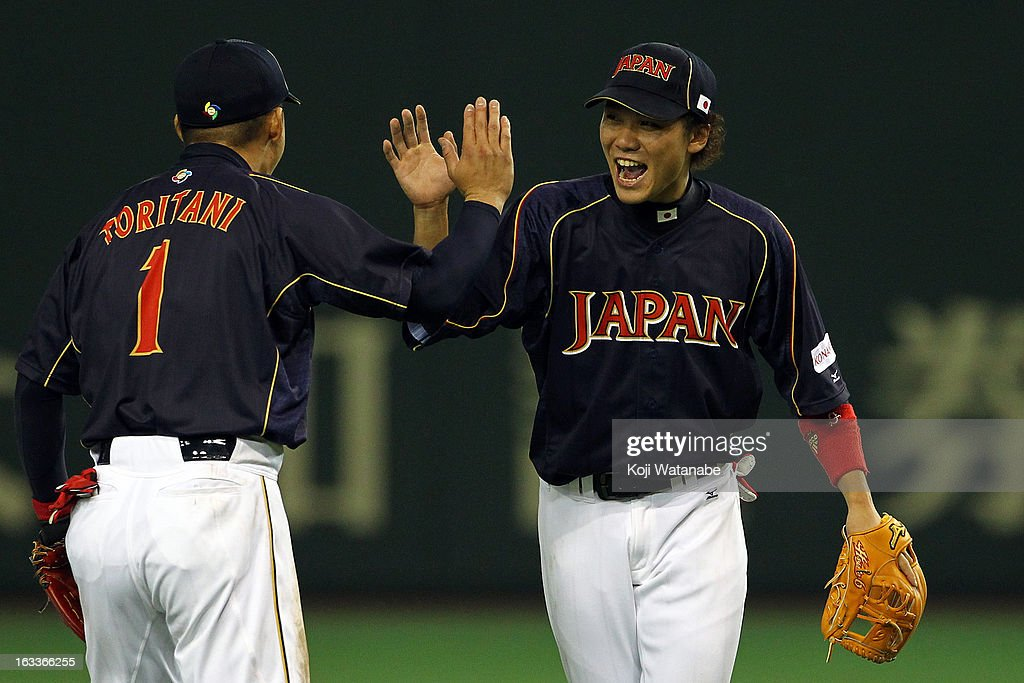 Infielder Hayato Sakamoto #6 and Takashi Toritani #1 of Japan celebrate after winning the World Baseball Classic Second Round Pool 1 game between Japan and Chinese Taipei at Tokyo Dome on March 8, 2013 in Tokyo, Japan.