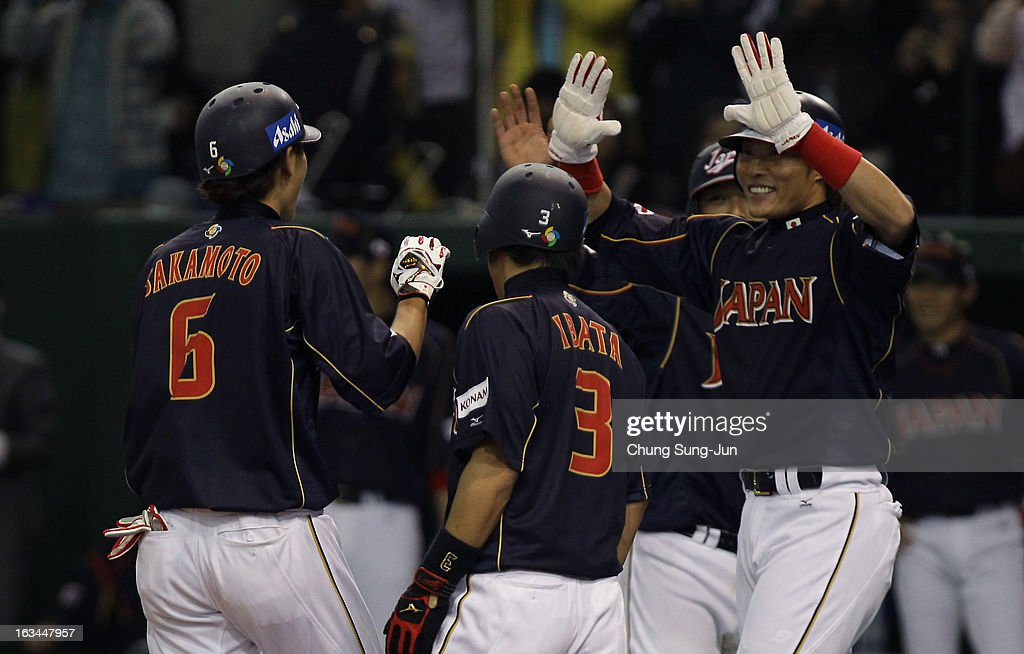 Infielder Hayato Sakamoto celebrates with Hirokazu Ibata and Yoshio Itoi of Japan after grand slam in the seventh inning during the World Baseball...