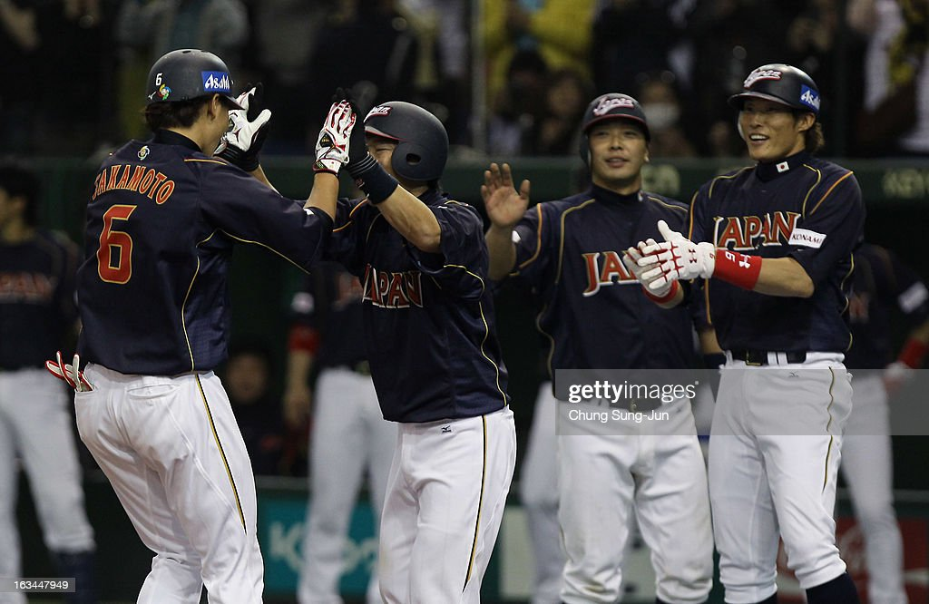 Infielder Hayato Sakamoto celebrates with Hirokazu Ibata Shinnosuke Abe and Yoshio Itoi of Japan after grand slam in the seventh inning during the...