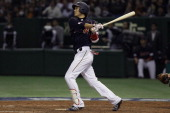 Infielder Hayato Sakamoto of Japan hits a grand slam in the seventh inning during the World Baseball Classic Second Round Pool 1 game between Japan...