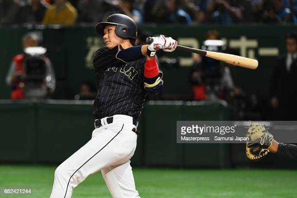 Infielder Hayato Sakamoto of Japan hits a single in the top of the fifth inning during the World Baseball Classic Pool E Game Two between Japan and...