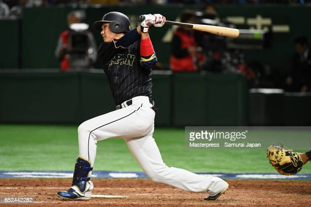 Infielder Hayato Sakamoto of Japan hits a single in the top of the ninth inning during the World Baseball Classic Pool E Game Two between Japan and...