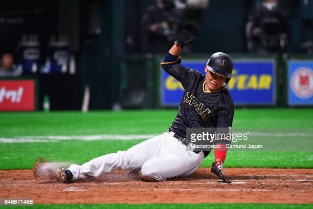 Infielder Hayato Sakamoto of Japan slides safely into the home plate after a sacrifice fly in the top of the fifth inning during the SAMURAI JAPAN...