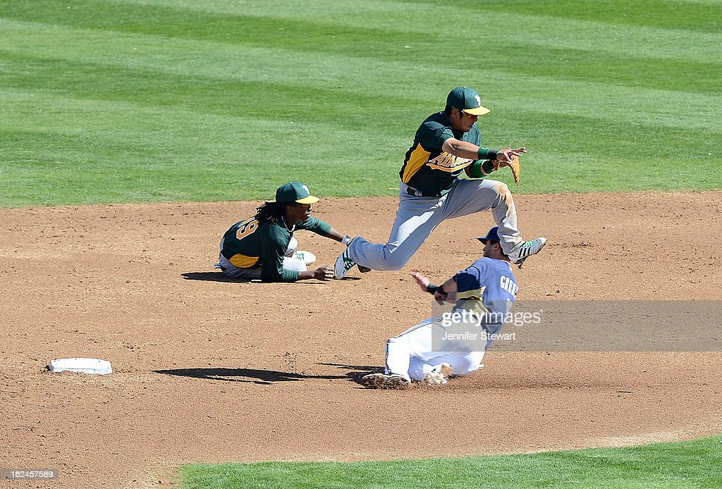 Infielder Hiroyuki Nakajima #3 of the Oakland Athletics jumps over the sliding Taylor Green #5 of the Milwaukee Brewers while turning a double play in the spring training game at Maryvale Baseball Park on February 23, 2013 in Phoenix, Arizona.