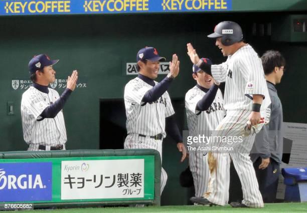 Infielder Hotaka Yamakawa of Japan high fives with Head coach Atsunori Inaba after scoring a run to make it 10 by the RBI double of Infielder Shuta...