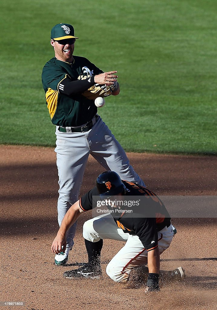 Infielder Jake Elmore #15 of the Oakland Athletics throws over the sliding <a gi-track='captionPersonalityLinkClicked' href=/galleries/search?phrase=Gary+Brown&family=editorial&specificpeople=196518 ng-click='$event.stopPropagation()'>Gary Brown</a> #56 of the San Francisco Giants to complete a double play during the fifth inning of the spring training game at Scottsdale Stadium on March 15, 2014 in Scottsdale, Arizona. The A's defeated the Giants 8-1.