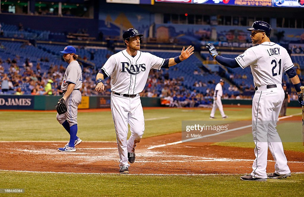 Infielder <a gi-track='captionPersonalityLinkClicked' href=/galleries/search?phrase=James+Loney&family=editorial&specificpeople=636293 ng-click='$event.stopPropagation()'>James Loney</a> #21 of the Tampa Bay Rays congratulates <a gi-track='captionPersonalityLinkClicked' href=/galleries/search?phrase=Ben+Zobrist&family=editorial&specificpeople=2120037 ng-click='$event.stopPropagation()'>Ben Zobrist</a> #18 after he scored on a wild pitch against the Toronto Blue Jays during the game at Tropicana Field on May 9, 2013 in St. Petersburg, Florida.