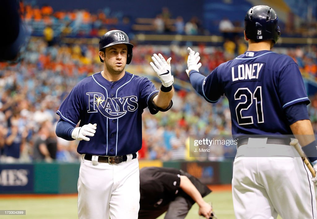 Infielder <a gi-track='captionPersonalityLinkClicked' href=/galleries/search?phrase=James+Loney&family=editorial&specificpeople=636293 ng-click='$event.stopPropagation()'>James Loney</a> #21 of the Tampa Bay Rays congratulates <a gi-track='captionPersonalityLinkClicked' href=/galleries/search?phrase=Evan+Longoria&family=editorial&specificpeople=2349329 ng-click='$event.stopPropagation()'>Evan Longoria</a> #3 after his solo sixth inning home run against the Minnesota Twins during the game at Tropicana Field on July 11, 2013 in St. Petersburg, Florida.