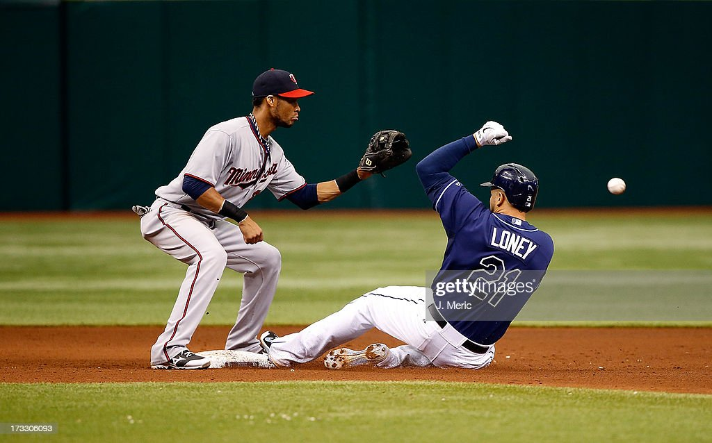 Infielder <a gi-track='captionPersonalityLinkClicked' href=/galleries/search?phrase=James+Loney&family=editorial&specificpeople=636293 ng-click='$event.stopPropagation()'>James Loney</a> #21 of the Tampa Bay Rays doubles in the sixth inning as shortstop Pedro Florimon #25 of the Minnesota Twins takes the throw during the game at Tropicana Field on July 11, 2013 in St. Petersburg, Florida.
