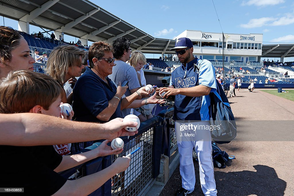 Infielder James Loney #21 of the Tampa Bay Rays signs some autographs during batting practice just before the Grapefruit League Spring Training Game against the Boston Red Sox at the Charlotte Sports Complex on March 10, 2013 in Port Charlotte, Florida.
