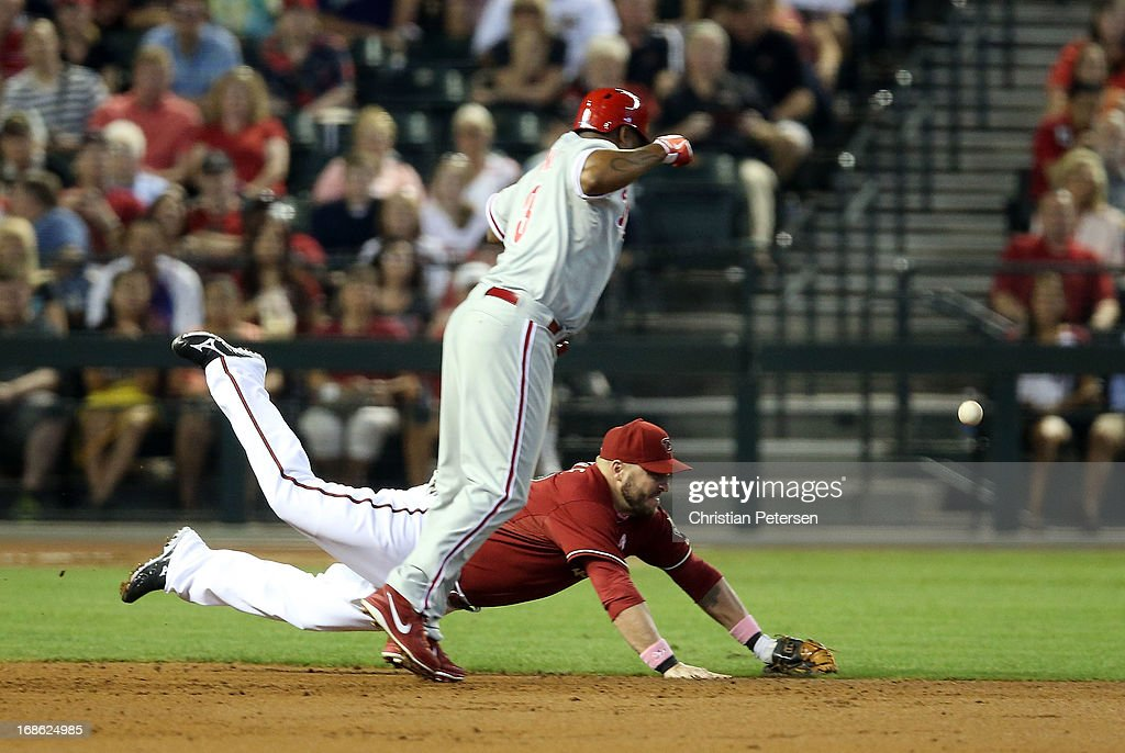 Infielder Jason Kubel #13 of the Arizona Diamondbacks dives for the ball on a fields choice out on Delmon Young #3 of the Philadelphia Phillies during the second inning of the MLB game at Chase Field on May 12, 2013 in Phoenix, Arizona.